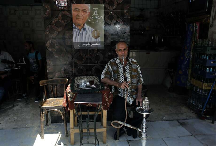 "An Egyptian man smokes a water pipe under a poster of presidential candidate, Ahmed Shafiq at a traditional coffee shop during the second day of the presidential runoff in Cairo, Egypt Sunday, June 17, 2012. Egyptians are choosing between a conservative Islamist and Hosni Mubarak's ex-prime minister in a second day of a presidential runoff that has been overshadowed by the domination of the country's military. Arabic on the poster reads, ""Ahmed Shafiq, President for Egypt, Egypt is for all."" (AP Photo/Nasser Nasser) Photo: Nasser Nasser, Associated Press"