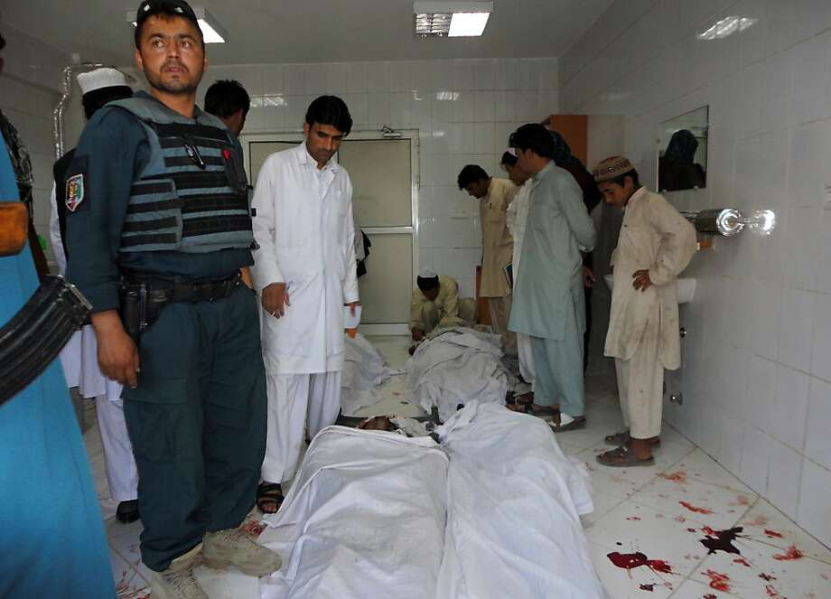 Afghan policeman and civilians gather at a hospital morgue holding the bodies of suicide bombing victims in Khost on June 20, 2012. A suicide bomber on a motorbike struck a joint Afghan-NATO patrol in the town of Khost on June 20, killing 17 Afghans and causing coalition casualties, officials said. The blast in the eastern town close to the border with Pakistan, where Taliban and other Islamist insurgents fighting US-led troops have strongholds, also wounded 37 people, hospital officials said. AFP PHOTO / STRSTRDEL/AFP/GettyImages Photo: Strdel, AFP/Getty Images