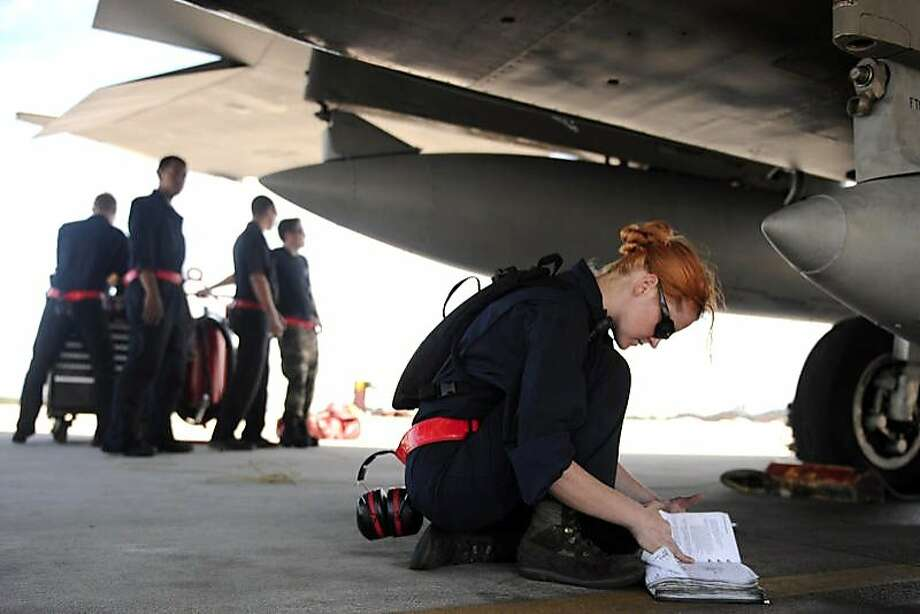 Airman 1st Class Jessica Hinves, US Air Force, kneels under an aircraft, from THE INVISIBLE WAR, a Cinedigm/Docurama Films release. Photo: Cinedigm