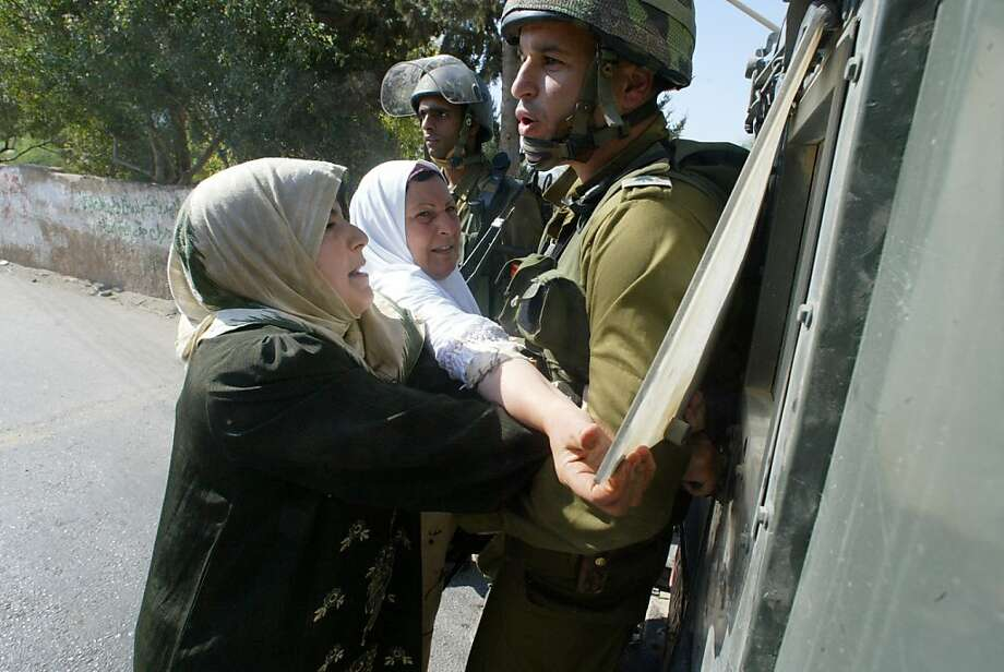 "Emad's mother pleads with an Israeli soldier to release her son Khaled after he was arrested in, ""5 Broken Cameras."". Photo: Kino Lorber"