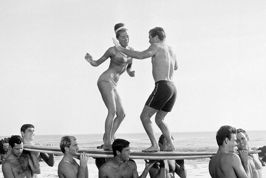 "FILE- In this January 5, 1965, file photo, actors in a Hollywood movie dance ""the twist"" in Malibu, Calif.  The Federal Reserve announced Wednesday, June 20, 2012, it is extending its ""Operation Twist"" program, which is named after the dance craze in an a nod to economic history when the Kennedy administration cut long-term rates while leavings short-term rates alone in the early 1960s.  The program is designed to spur borrowing and spending. (AP Photo) Photo: Dad"