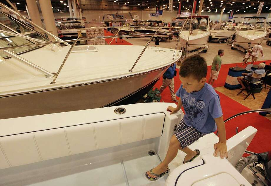 Hyden Bate, 7, climbs the Carolina Classic 28 boat during the 25th Annual Houston Summer Boat Show at Reliant Center. Photo: Mayra Beltran, Houston Chronicle / © 2012 Houston Chronicle