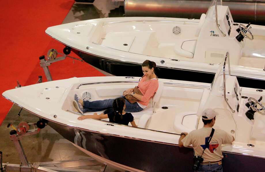 Lisa Burke rests on a boat while attending the 25th Annual Houston Summer Boat Show. Photo: Mayra Beltran, Houston Chronicle / © 2012 Houston Chronicle