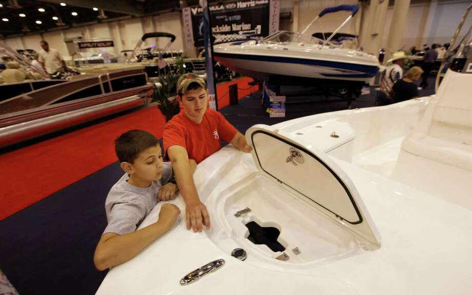 Michael Justice, 12, listens to his brother Jacob Justice, 18, while viewing a bay boat during the 25th Annual Houston Summer Boat Show at Reliant Center. Photo: Mayra Beltran, Houston Chronicle / © 2012 Houston Chronicle