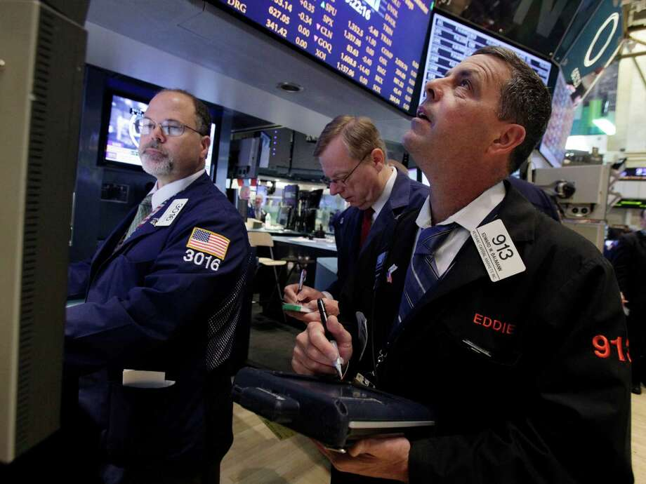 Trader Edward Baumann, right, works on the floor of the New York Stock Exchange Wednesday, June 20, 2012. Stocks edged lower early Wednesday after investors saw signs that economies could be slowing down in both the West and China. (AP Photo/Richard Drew) Photo: Richard Drew