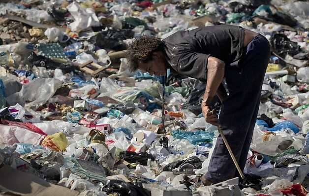 In this photo taken on Monday, June 18, 2012, a man looks for valuable items in a pile of trash by the Jacare river, one of the most polluted rivers in the country, at Manguinhos slum in Rio de Janeiro, Brazil.  The throngs streaming into Rio for the United Nations Conference on Sustainable Development or Rio+20 may be dreaming of white-sand beaches and clear, blue waters, but what they are first likely to notice as they leave the airport is not the salty tang of ocean in the breeze, but the stench of raw sewage. (AP Photo/Victor R. Caivano) Photo: Victor R. Caivano, Associated Press
