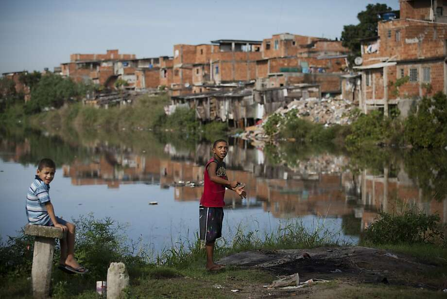 In this photo taken on Monday, June 18, 2012, children fly kites by the Jacare River, one of the most polluted rivers in the country, at Manguinhos slum in Rio de Janeiro, Brazil. The throngs streaming into Rio for the United Nations Conference on Sustainable Development or Rio+20 may be dreaming of white-sand beaches and clear, blue waters, but what they are first likely to notice as they leave the airport is not the salty tang of ocean in the breeze, but the stench of raw sewage. (AP Photo/Victor R. Caivano) Photo: Victor R. Caivano, Associated Press