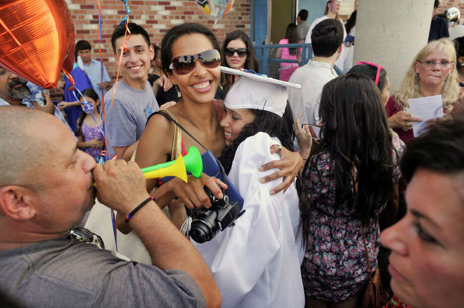 Humberto Gandra, left, blows a horn as Marly Lemos hugs their daughter, Luiza Gandra, following the graduation ceremony at Danbury High School on Wednesday, June 20, 2012. Photo: Jason Rearick / The News-Times