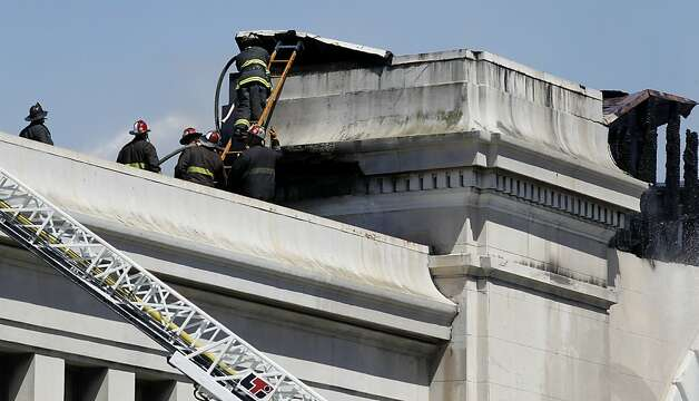 Firefighters climb to the top of the roof to battle a four-alarm blaze that severely damaged Pier 29 in San Francisco, Calif. on Wednesday, June 20, 2012. Photo: Paul Chinn, The Chronicle