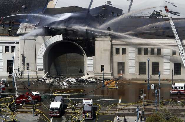 Firefighters spray down Pier 29 after a fire there in San Francisco, Calif., Wednesday, June 20, 2012. Photo: Sarah Rice, Special To The Chronicle