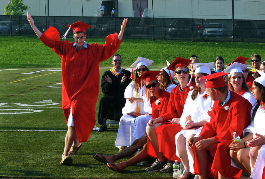 Graduate Scott Cerick waves his arms to get the crowd excited as he goes up to get his degree, during New Canaan High School's Class of 2012 Graduation Ceremony in New Canaan, Conn. on Wednesday June 20, 2012. Cerick was the very last graduate to go up because the school officials couldn't find his degree earlier when he went up. Photo: Christian Abraham / Connecticut Post