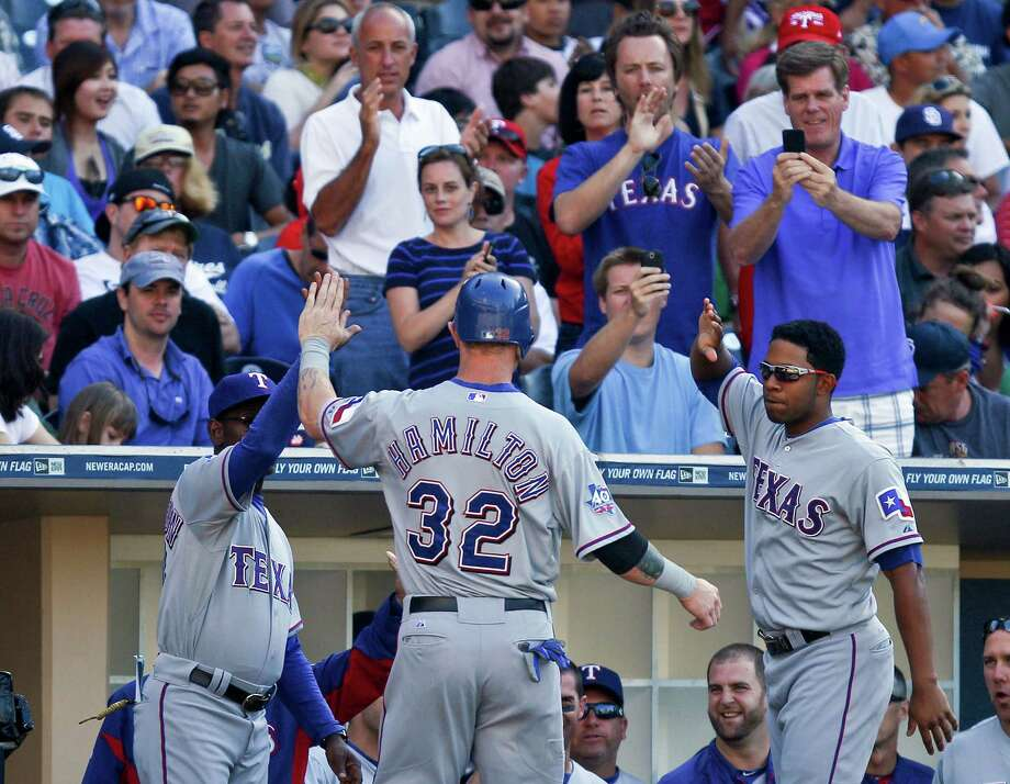 Texas Rangers' Josh Hamilton is congratulated at the dugout after scoring against the San Diego Padres during the sixth inning of a baseball game Wednesday, June 20, 2012, in San Diego. Photo: AP