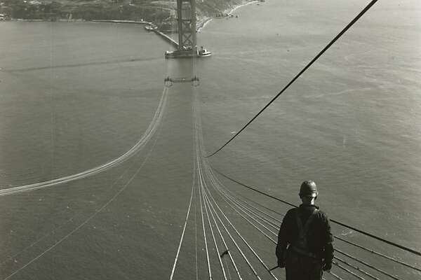 1936 - A bridge worker looks across to the San Francisco tower as cables are spun for the Golden Gate Bridge.