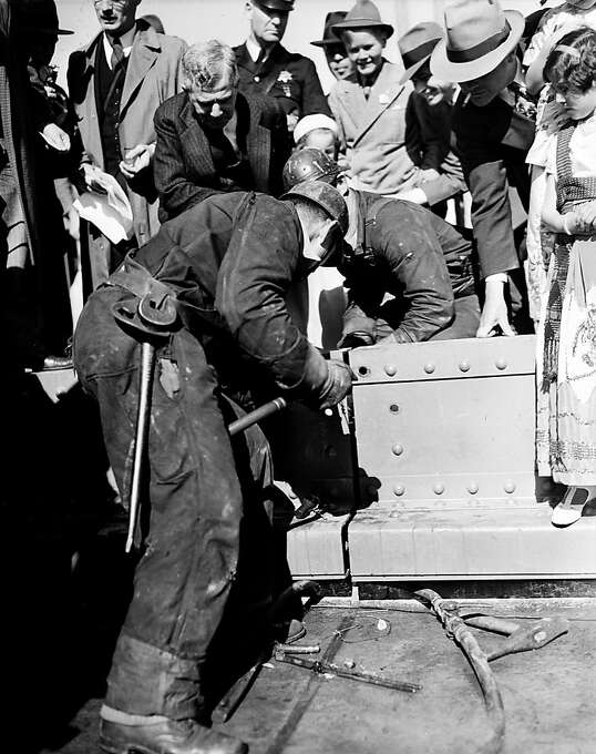 Ed Stanley drives the golden rivet to mark the completion of the $35,000,000 Golden Gate Bridge spanning the entrance to San Francisco Bay, Ca., April 29, 1937. Holding the rivet is Ed Murphy and leaning over them is Joseph B. Strauss, chief engineer of the project. Photo: AP