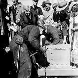 Ed Stanley drives the golden rivet to mark the completion of the $35,000,000 Golden Gate Bridge spanning the entrance to San Francisco Bay, Ca., April 29, 1937. Holding the rivet is Ed Murphy and leaning over them is Joseph B. Strauss, chief engineer of the project.