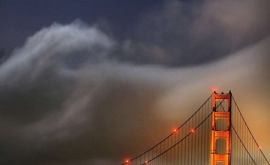 The evening fog curled up in a ball like cotton candy as a near full moon cast a broad beam of light that spread over The Golden Gate Bridge .May 7, 2009. Photo: Frederic Larson, The Chronicle