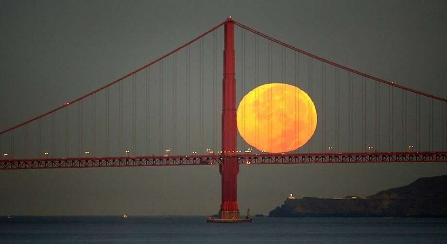 The full moon set seemingly on the deck of the Golden Gate Bridge during Wednesday commute hour (6:35am) seen from Treasure Island on September 26, 2007. Photo: Frederic Larson, The Chronicle