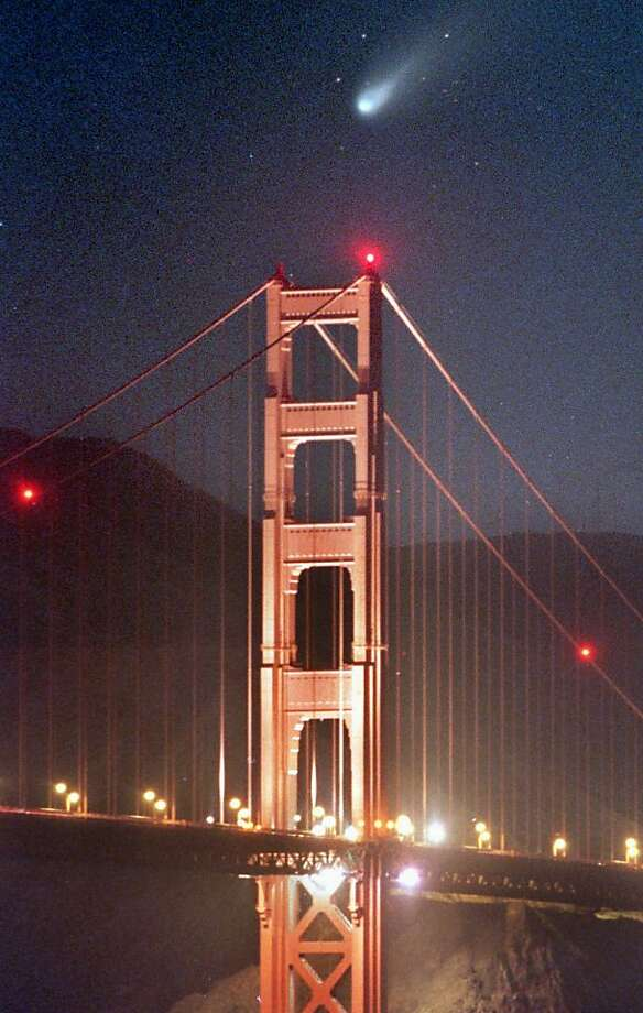 The comet Hale-Bopp is seen low on the horizon Wednesday evening, March 26, 1997 looking northwest over San Francisco's Golden Gate bridge. This photo was made with a 300mm lens exposed with a lens opening of F2.8 for 15 seconds on 800 ASA film pushed one stop. Photo: Frederic Larson, The Chronicle