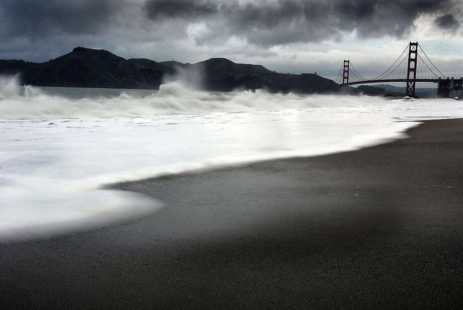 The morning rains stirred up the ocean at Bakers Beach as heavy dark rain clouds moved in over the hills of Marin and the Golden Gate Bridge. 4/7/05 Photo: Frederic Larson, The Chronicle
