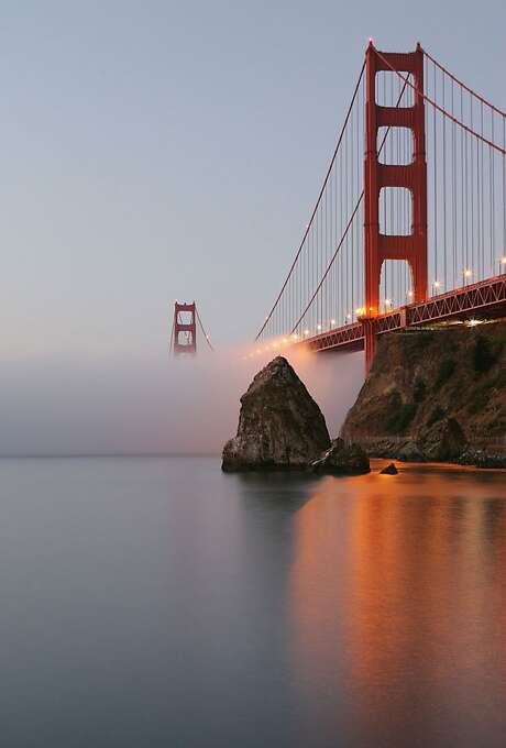 The September low hugging fog slowly makes its way under the Golden Gate Bridge seen at Fort Baker during sunrise. Photo: Frederic Larson, The Chronicle