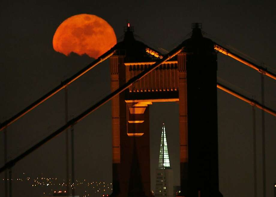 A full moon rises over the Golden Gate Bridge as the bridge's north tower frames the TransAmerica Pyramid on April 20, 2008. Photo: Frederic Larson, The Chronicle