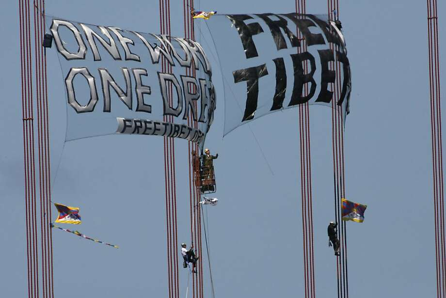 After three demonstrators unfurl banners in protest of China's crackdown in Tibet after scaling the south tower of the Golden Gate Bridge this morning a bridge worker cut the banner (top center) on April 7, 2008. Photo: Frederic Larson, The Chronicle