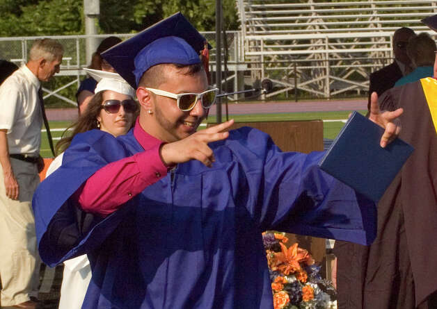 Cesar Martinez waves to family and friends after receiving his diploma during the graduation ceremony at Danbury High School on Wednesday, June 20, 2012. Photo: Jason Rearick / The News-Times