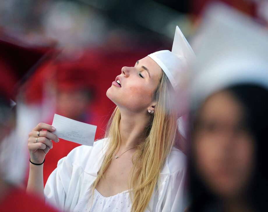 Graduating senior Erin David, 18, uses an index card in an attempt to stay cool during the Greenwich High School 2012 commencement at Cardinal Stadium Wednesday night, June 20, 2012. Photo: Bob Luckey / Greenwich Time