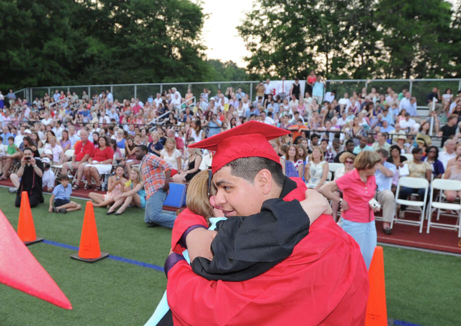 Graduating senior Andres Ortiz, 17, gets a hug during the Greenwich High School 2012 commencement at Cardinal Stadium Wednesday night, June 20, 2012. Ortiz said he will be attending Norwalk Community College. Photo: Bob Luckey / Greenwich Time