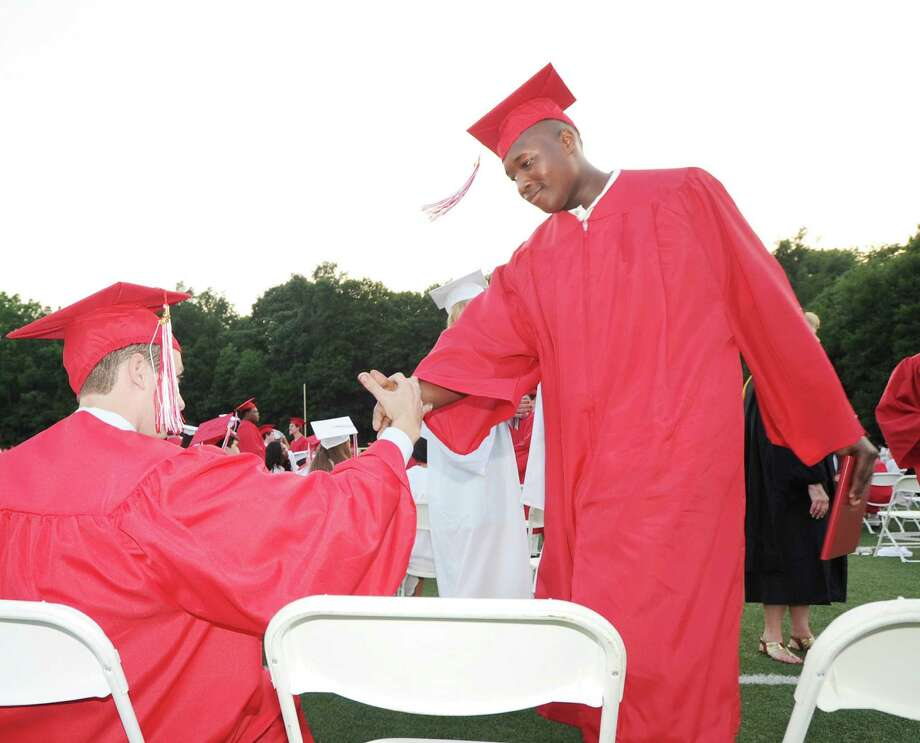 At right, Shaun Perry, 17, slaps hands with a fellow graduate after receiving his diploma during the Greenwich High School 2012 commencement at Cardinal Stadium Wednesday night, June 20, 2012. Perry said he will start out his higher education by attending Norwalk Community College. Photo: Bob Luckey / Greenwich Time