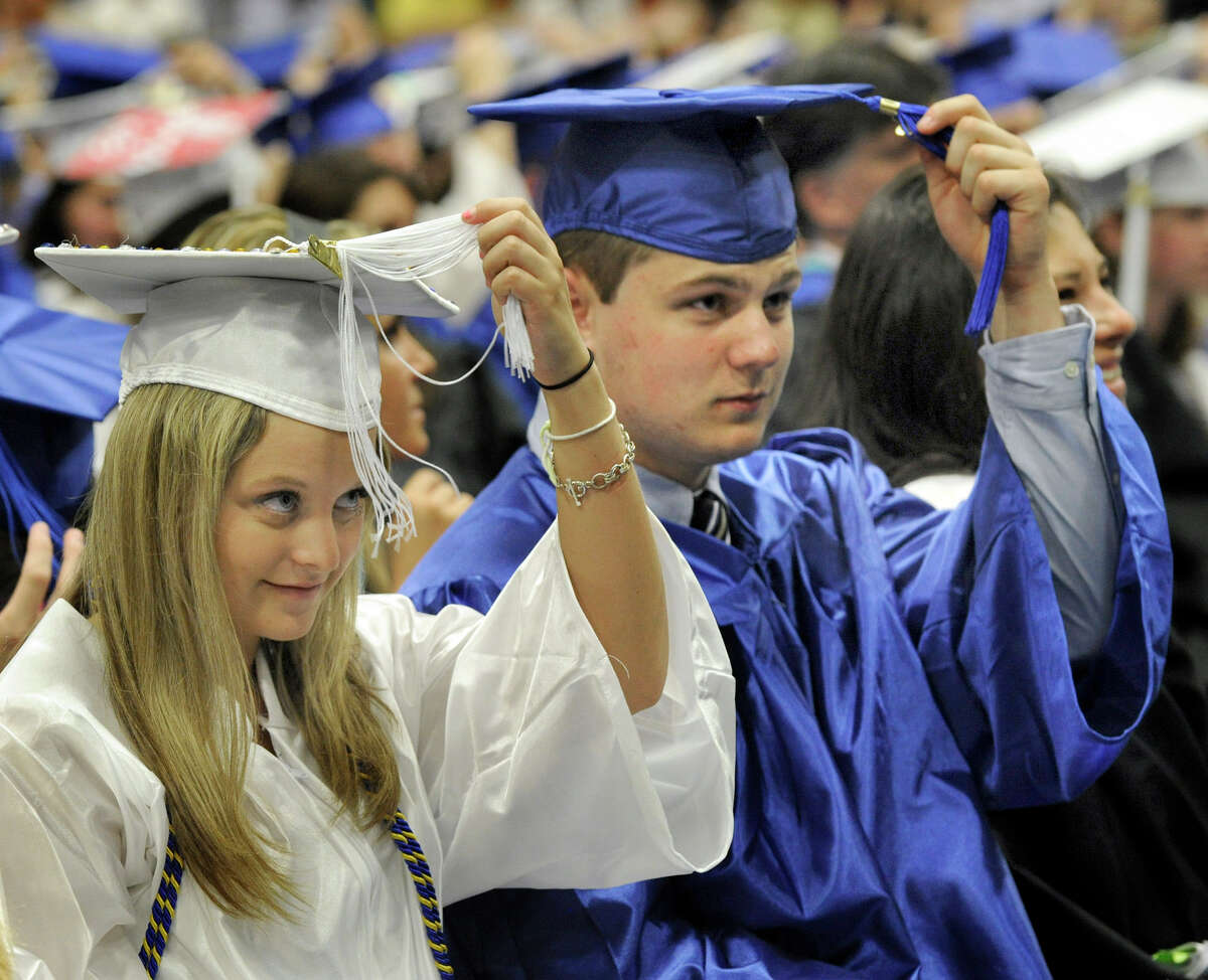 Brooke Leifels, left, and Ryan LeMay, move their tassels at the end of Newtown High School's commencement exercises held at Western Connecticut State University's O'Neill Center, Wednesday, June 20, 2012.