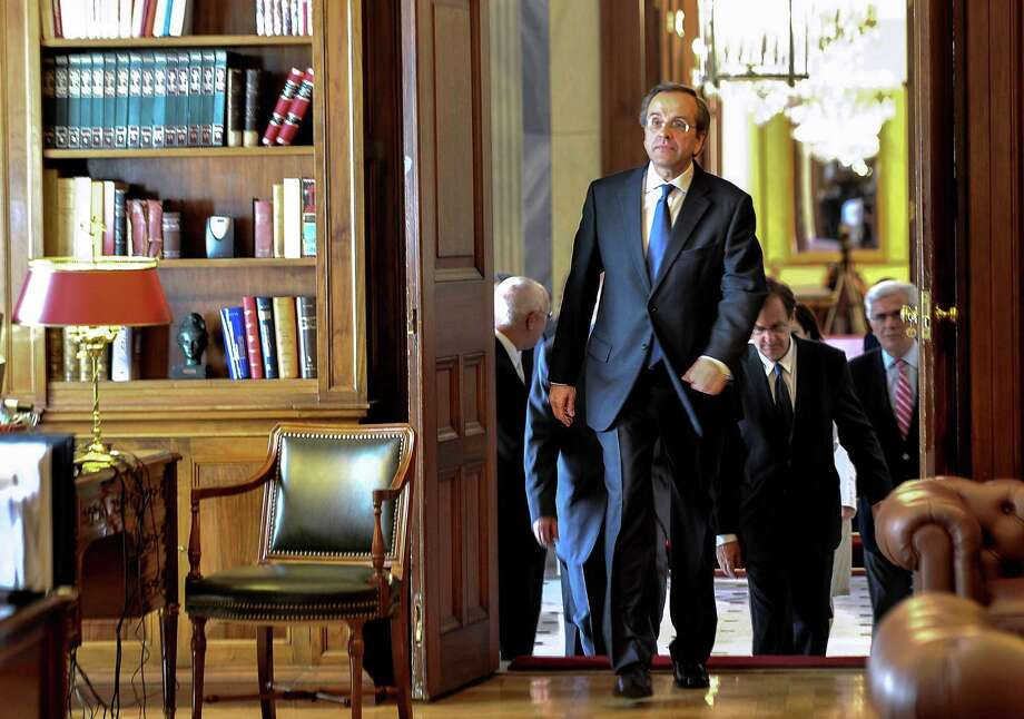 The head of Greece's conservative New Democracy party, Antonis Samaras, enters the President's office to take the mandate to form the new government in Athens on Wednesday June 20, 2012.   Samaras was sworn in as prime minister Wednesday at the helm of a three-party coalition that will uphold the country's international bailout commitments. The move ends a protracted political crisis that had cast grave doubt over the country's future in Europe's joint currency and threatened to plunge Europe deeper into a financial crisis with global repercussions. (AP Photo/Andreas Solaro,pool) Photo: Andreas Solaro