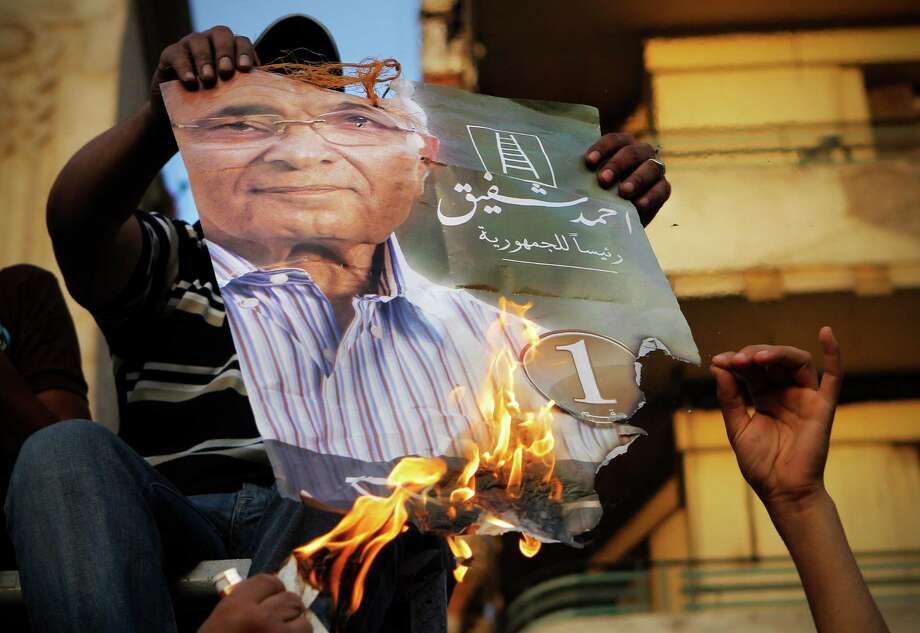 "Muslim brotherhood's presidential candidate Mohammed Morsi supporters burn a poster for presidential candidate Ahmed Shafiq, in Tahrir Square, the focal point of Egyptian uprising, in Cairo, Egypt, Tuesday, June 19, 2012. The Brotherhood has called for mass demonstrations in Cairo and elsewhere on Tuesday to protest the interim charter issued by the military as well as a court ruling last week that dissolved parliament, where the Brotherhood controlled nearly half the seats. Already, several thousand protesters have gathered in Cairo's Tahrir Square, birthplace of the uprising that toppled Mubarak 16 months ago. Arabic on the poster reads, ""Ahmed Shafiq for Egyptian presidency."" (AP Photo/Amr Nabil) Photo: Amr Nabil"