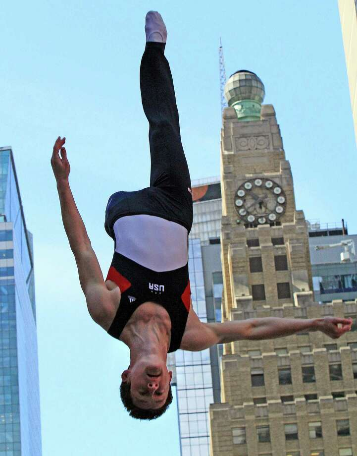 FILE - This April 18, 2012 file photo shows gymnast Jeffrey Gluckstein performing on a trampoline in New York's Times Square during U.S. Olympic Team festivities marking 100 days until the London Olympics. Steven Gluckstein spent his childhood two steps ahead of younger brother Jeffrey, clicking off each of life's major milestones first. Now, however, Jeffrey can snatch way an important one: Olympian. (AP Photo/Bebeto Matthews, File) Photo: Bebeto Matthews
