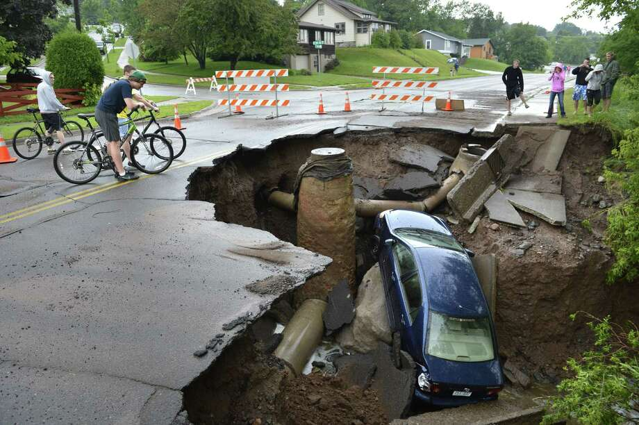 A car sits in a giant sinkhole in Duluth, Minn. Wednesday, June 19, 2011. Residents evacuated their homes and animals escaped from pens at a zoo as floods fed by a steady torrential downpour struck northeastern Minnesota, inundating the city of Duluth, officials said Wednesday. Photo: Brian Peterson, Associated Press / Brian Peterson