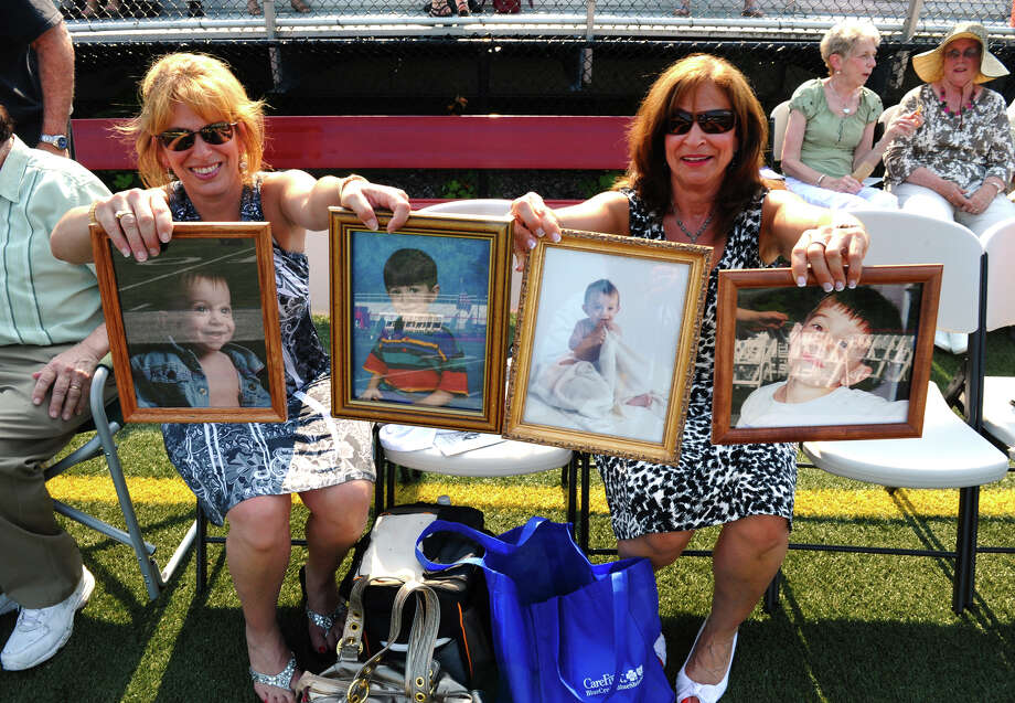 Family members Beth Sinko, left, and Susan Cooper, hold up photos of graduate Michael DeMattia, during New Canaan High School's Class of 2012 Graduation Ceremony in New Canaan, Conn. on Wednesday June 20, 2012. Beth is Michael's  aunt and Susan is his mom. Photo: Christian Abraham / Connecticut Post