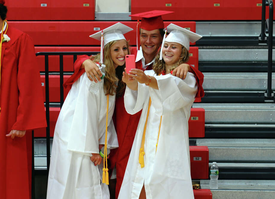 Graduates Tess Litchman, left, Lachlan Lancaster, center, and Emily Lambdin, snap photos of themselves, before the start of New Canaan High School's Class of 2012 Graduation Ceremony in New Canaan, Conn. on Wednesday June 20, 2012. Photo: Christian Abraham / Connecticut Post