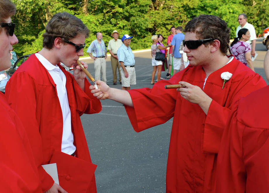 Graduates Cameron McSorley, left, and Andrew Reznik enjoy celebratory cigars after the conclusion of New Canaan High School's Class of 2012 Graduation Ceremony in New Canaan, Conn. on Wednesday June 20, 2012. Photo: Christian Abraham / Connecticut Post