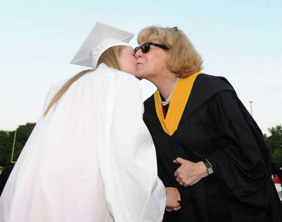 GHS English teacher Ellen Johnsmeyer, right, hugs a graduate durng the Greenwich High School 2012 commencement at Cardinal Stadium Wednesday night, June 20, 2012. Photo: Bob Luckey / Greenwich Time