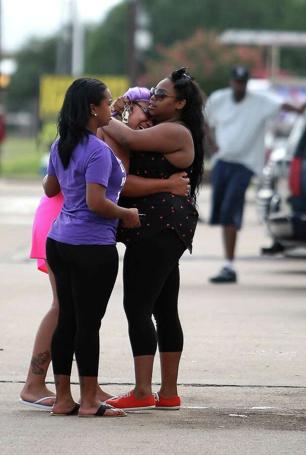 Unidentified family and friends react during  a vigil at the scene of a strip club where three people were shot to death and two were injured including local rapper Trae Tha Truth, early Wednesday morning, Wednesday, June 20, 2012, in Houston. Photo: Karen Warren, Houston Chronicle / © 2012  Houston Chronicle