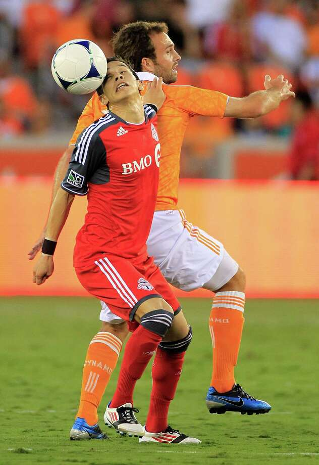Toronto FC's Eric Avila, left, beats Houston Dynamo's Adam Moffat, right, to a header during the first half of a soccer game against the Houston Dynamo at BBVA Compass Stadium Wednesday, June 20, 2012, in Houston. Photo: Cody Duty, Houston Chronicle / © 2011 Houston Chronicle