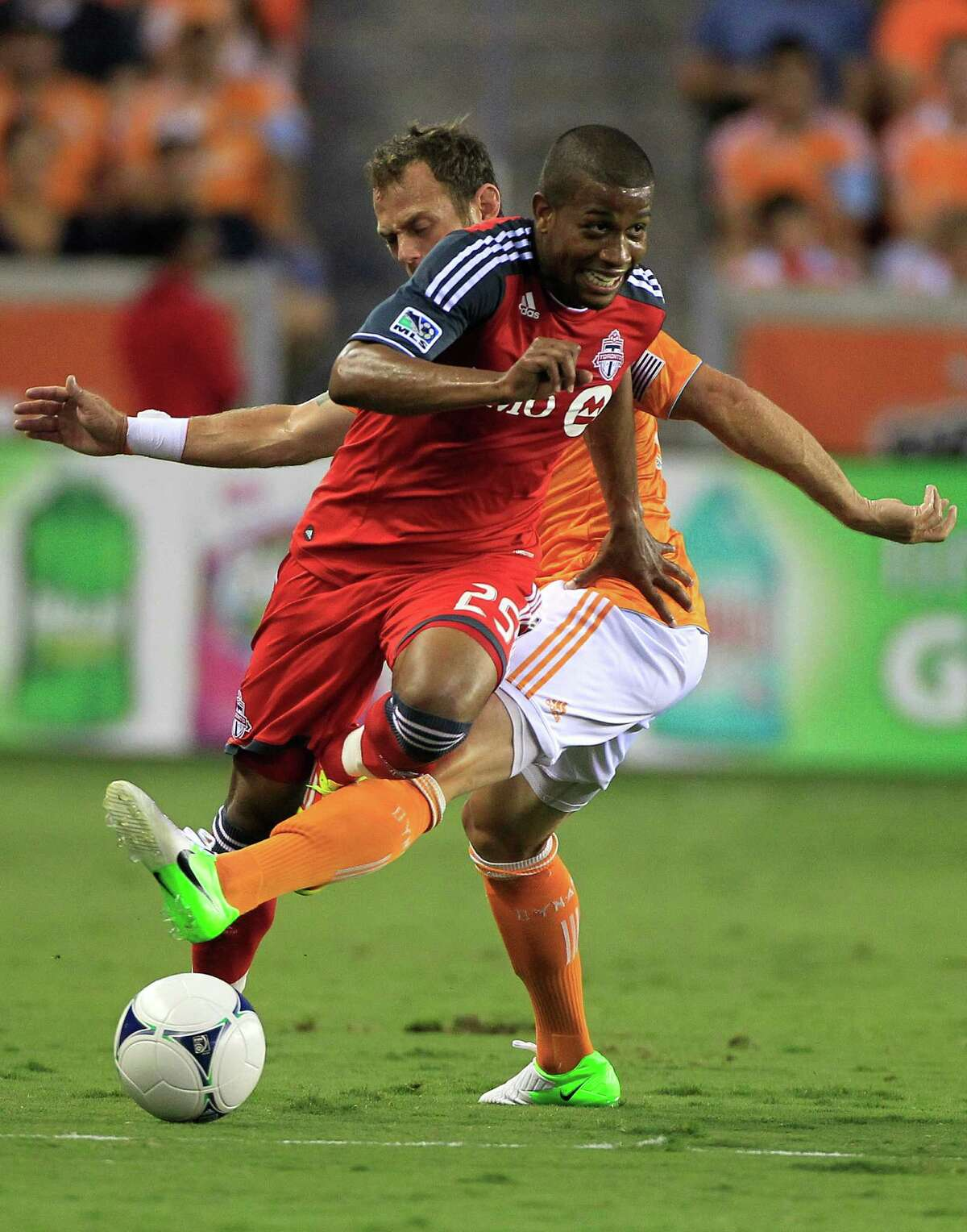 Toronto FC's Jeremy Hall, left, is tripped up by Houston Dynamo's Brad Davis, right, during the first half of a soccer game against the Houston Dynamo at BBVA Compass Stadium Wednesday, June 20, 2012, in Houston.