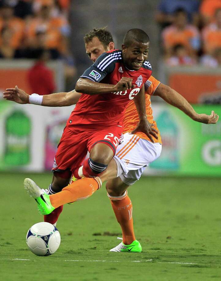Toronto FC's Jeremy Hall, left, is tripped up by Houston Dynamo's Brad Davis, right, during the first half of a soccer game against the Houston Dynamo at BBVA Compass Stadium Wednesday, June 20, 2012, in Houston. Photo: Cody Duty, Houston Chronicle / © 2011 Houston Chronicle