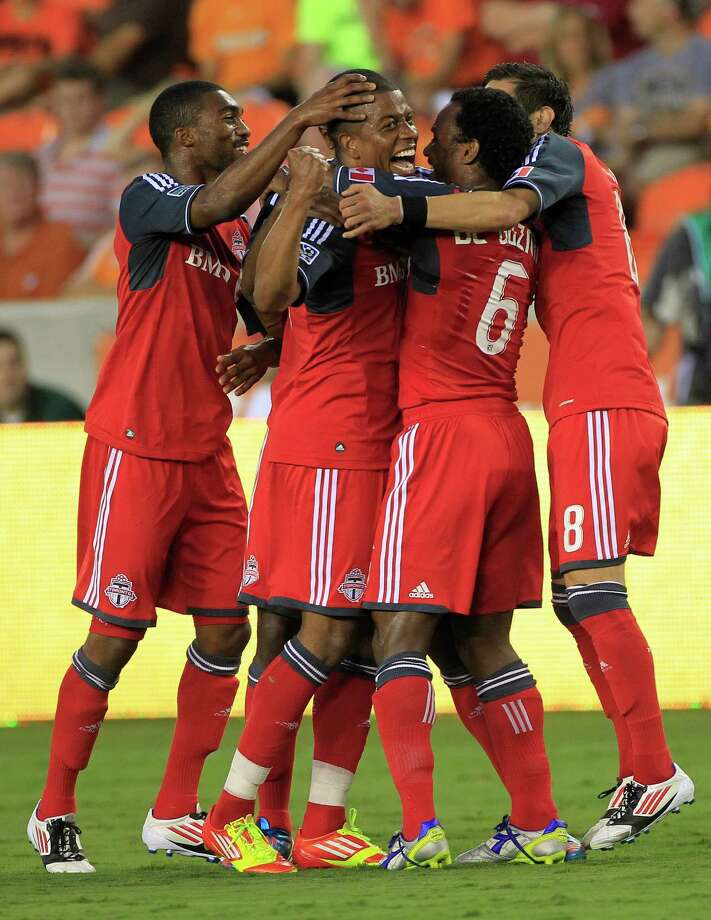 Toronto FC's, from left, Ashtone Morgan, Jeremy Hall, Julian de Guzman and Eric Avila, celebrate after Hall scored a goal during the fist half of a soccer game against the Houston Dynamo at BBVA Compass Stadium Wednesday, June 20, 2012, in Houston. Photo: Cody Duty, Houston Chronicle / © 2011 Houston Chronicle