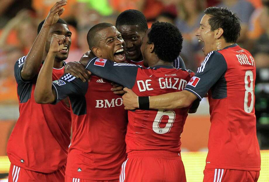 Toronto FC's, from left, Ashtone Morgan, Jeremy Hall, Doneil Henry, Julian de Guzman and Eric Avila, celebrate after Hall scored a goal during the fist half of a soccer game against the Houston Dynamo at BBVA Compass Stadium Wednesday, June 20, 2012, in Houston. Photo: Cody Duty, Houston Chronicle / © 2011 Houston Chronicle