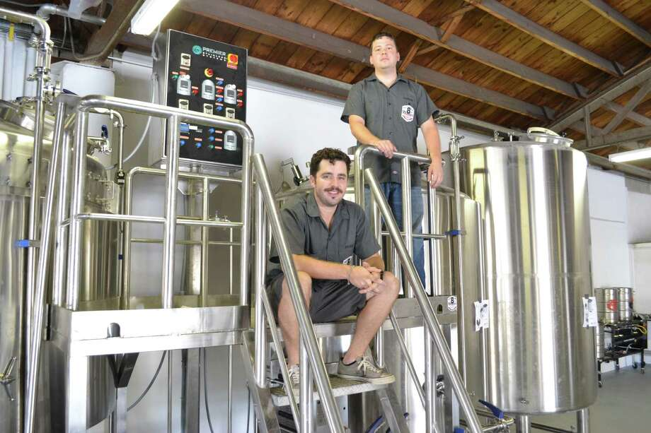 Ryan Soroka, left, and brewer Aaron Corsi of the 8th Wonder Brewing Co. in EaDo passed another milestone toward opening by installing this automated,  20-barrel brewhouse. Photo: Ronnie Crocker / Houston Chronicle