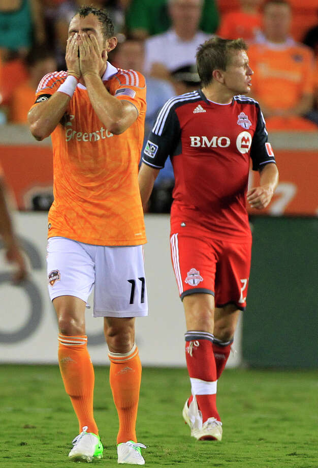 Houston Dynamo's Brad Davis, left, reacts as Toronto FC's Terry Dunfield, right, looks on during the first half of a soccer game against the Houston Dynamo at BBVA Compass Stadium Wednesday, June 20, 2012, in Houston. Photo: Cody Duty, Houston Chronicle / © 2011 Houston Chronicle