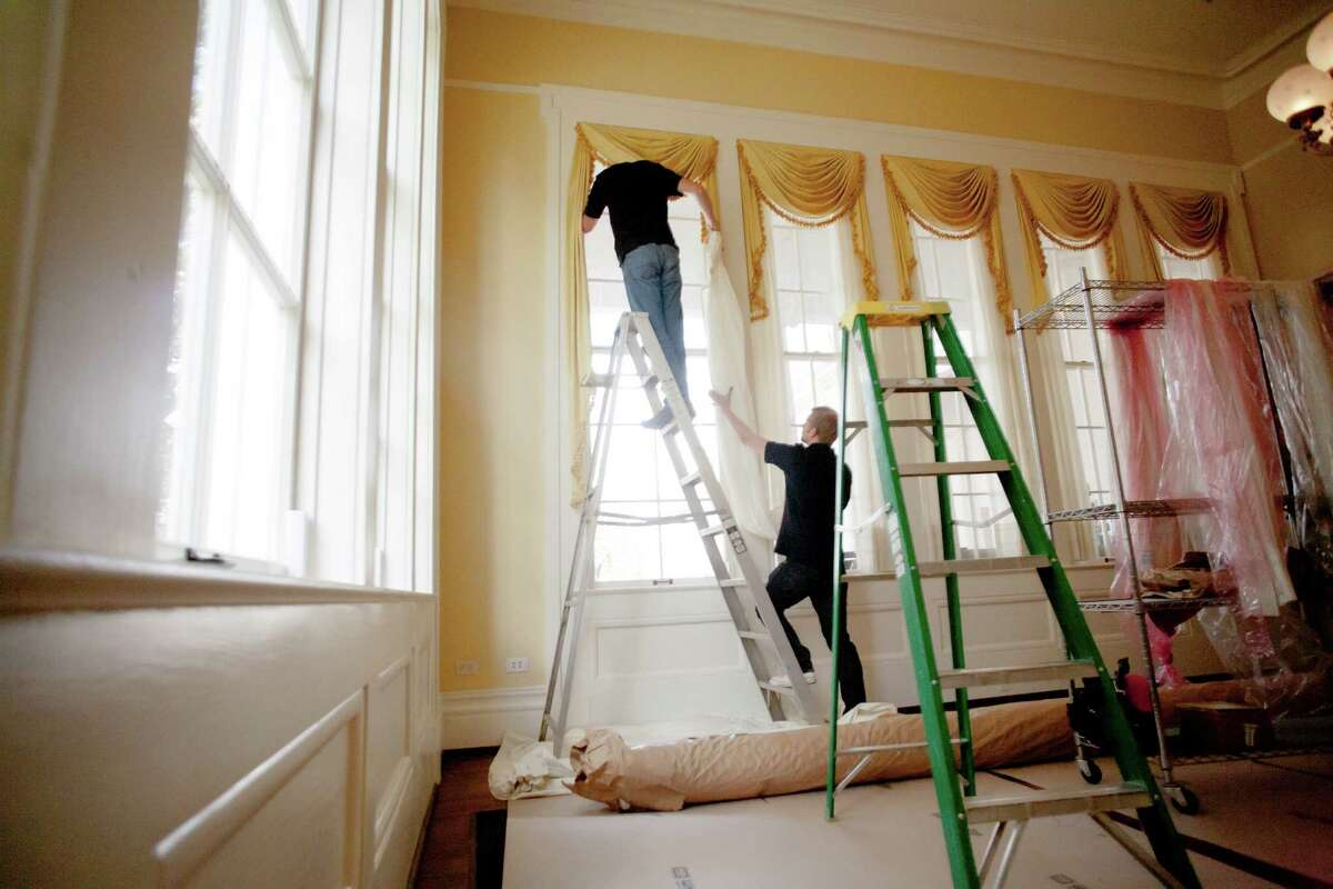Scott Wengert, left, and Patrick Roberts rehang drapes in the Governor's Mansion on Wednesday in Austin.