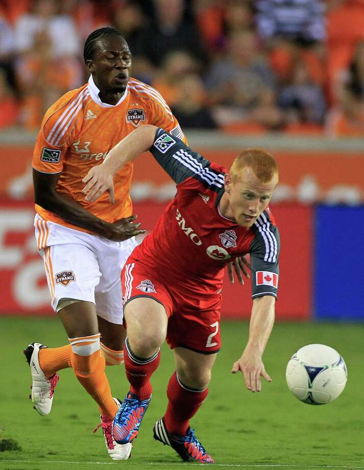 Houston Dynamo's Macoumba Kandji, left, is outrun by Toronto FC's Richard Eckersley, right, during the first half of a soccer game at BBVA Compass Stadium Wednesday, June 20, 2012, in Houston. The game ended in a 3-3 draw. Photo: Cody Duty, Houston Chronicle / © 2011 Houston Chronicle