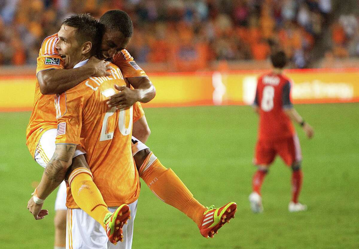 Houston Dynamo's Corey Ashe, right, hugs Geoff Cameron, left, after teammate, Will Bruin, scored a goal against Toronto FC during the second half of a soccer game at BBVA Compass Stadium Wednesday, June 20, 2012, in Houston. The game ended in a 3-3 draw.